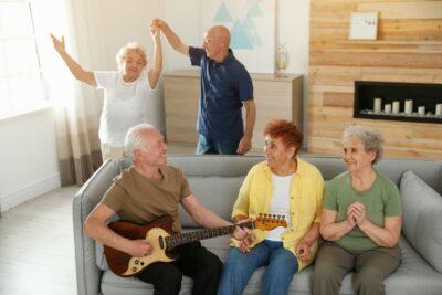 Oudere man die gitaar speelt voor zijn vrienden in de woonkamer